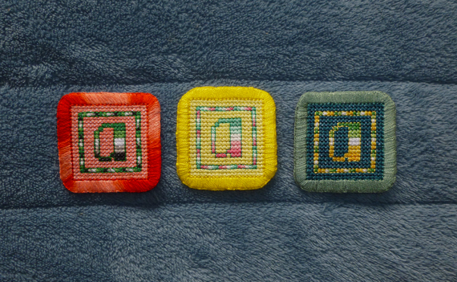 "A row of three square ""a"" cross stitch patches sitting on a blue microfibre blanket. All three patches feature the lower-case letter ""a"", stitched in the horizontal stripes of a pride flag, surrounded by a coloured frame on a plain-coloured background, the edges of the patch finished in a thick buttonhole stitch. From left to right: aromantic on coral background with mottled red border; abro on lemon background with yellow border; and allo-aro on teal background with a green-grey border."