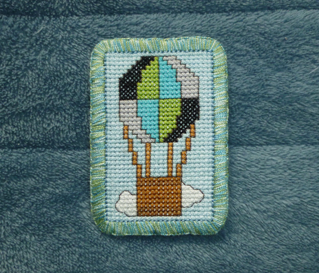 A rectangular cross stitch patch sitting on a blue microfibre blanket. The patch features a hot air balloon with a brown basket on a light blue sky background. A white cloud sits behind the basket. The balloon is quartered into eight sections, stitched in the black, green, blue and grey of the quoiromantic flag. The patch has a hand-embroidered edge sewn in a mottled blue, green and grey floss.