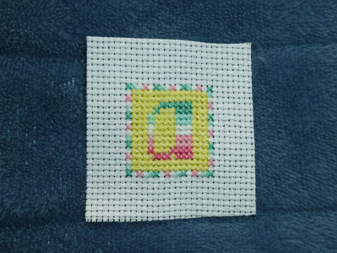 "A square ""a"" patch in progress, sitting on a blue microfibre blanket. The letter ""a"" in abro pride stripes sits in the middle of a yellow square block of stitching. The beginnings of a one-stitch-wide square frame, in stitches alternating the colours of the abro flag, surrounds the yellow block. All the colours of the abro flag have been sewn into the border save the final dark pink stripe."