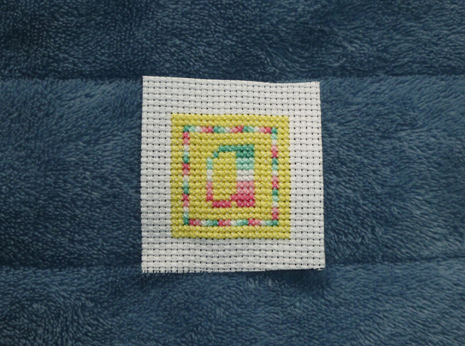 "A square ""a"" patch in progress, sitting on a blue microfibre blanket. The letter ""a"" in abro pride stripes sits in the middle of a yellow square block of stitching, surrounded by a one-stitch-wide square border, the stitches alternating the colours of the abro flag. A second yellow border, the same colour as the middle yellow block, frames the flag-stripe border so that the ""a"" and flag border appear to sit in the middle of a large yellow square."