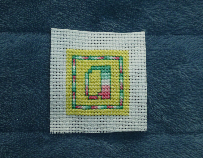 "A square ""a"" patch in progress, sitting on a blue microfibre blanket. The letter ""a"" in abro pride stripes sits in the middle of a yellow square block of stitching, surrounded by a one-stitch-wide square border, the stitches alternating the colours of the abro flag. A second yellow border, the same colour as the middle yellow block, frames the flag-stripe border so that the ""a"" and flag border appear to sit in the middle of a large yellow square. Both border and letter are outlined in dark green backstitch."