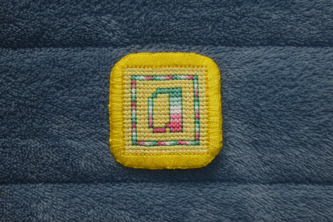 "A square ""a"" patch sitting on a blue microfibre blanket. The letter ""a"" in abro pride stripes sits in the middle of a yellow square block of stitching, surrounded by a one-stitch-wide square frame, the stitches alternating the colours of the abro flag. Both frame and letter are outlined in dark green backstitch, and the patch is finished in a bright yellow buttonhole stitch border."