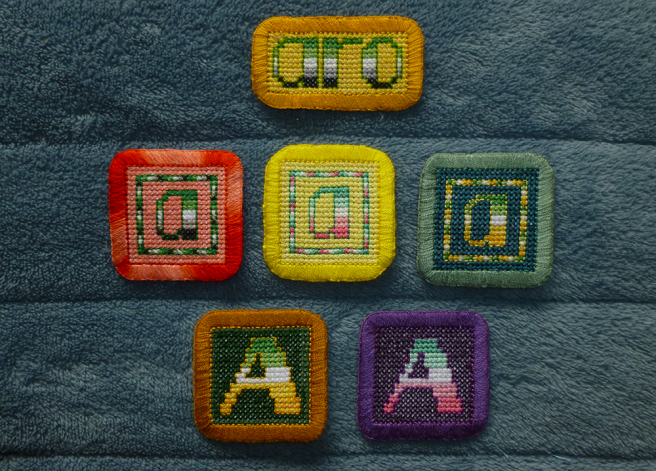 "Six cross stitch patches sitting on a blue microfibre blanket. First row: a rectangular patch with the text ""aro"" in lower-case embroidered in the stripes of the aro flag against a yellow background with a gold border. Second row three square lower-case ""a"" cross stitch patches, embroidered in the stripes of the aro (coral background/red border), abro (lemon background/yellow border) and allo-aro (teal background/blue-grey border) flags. Second row: two upper-case ""A"" patches, embroidered in the stripes of the aro (pine-green background/gold border) and abro (dark violet background, violet border) flags."