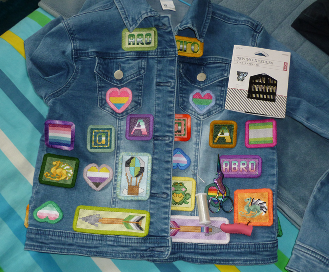 "A light wash, blue, cropped denim jacket sitting on a blue, white, yellow, green, navy and cyan striped quilt cover. The front of the jacket is covered in an assortment of handsewn cross stitch patches, including the letters ""A"" in pride flag stripes, two arrow designs, hearts in various flag stripes, a frog, two dragons, a hot air balloon, the word ""abro"" and the words ""aro"" in upper and lower case type. A needle sitting atop the jacket beside a spool of clear nylon thread shows the sewing down of the patches in progress."