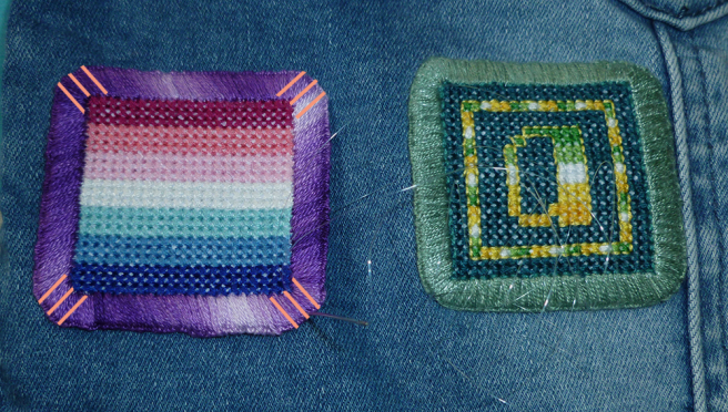 "A close-up photo of a front pannel from the denin jacket, showing two patches set side by side: a nebularomantic flag square with a variegated purple border; and an allo-aro letter ""a"" patch with a grey-green border. A needle threaded with clear nylon thread--like very fine fishing line--is set in the corner of the nebularomantic patch, and sets of three lines on orange have been photoshopped into the corners, indicating where one should tack down the patch."