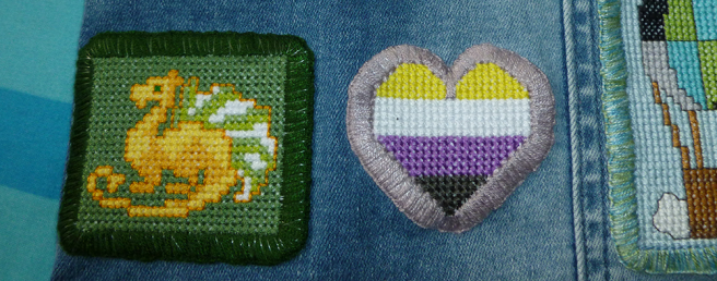 A cropped photo of two patches attached to a denim jacket--one a gold dragon on a green background with a dark green border, the other a non-binary flag heart with a lavender border. The clear nylon thread attaching the heart to the jacket is only just visible amongst the lavender floss, but stands out more obviously amongst the dark green on the dragon patch.