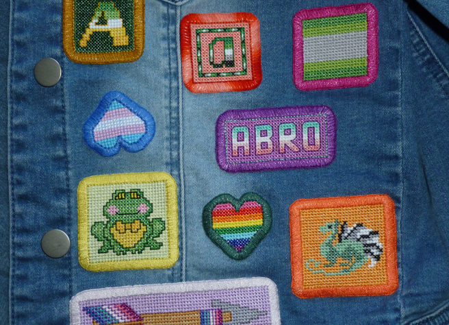 "A close-up photo of a front pannel from the denin jacket, showing various patches aligned to the button placket and the flat felled seam. Patches include a frog on a yellow background, a rectangular nebula arrow, a rainbow heart, a dragon on an orange background, a rectangular patch reading ""abro"", an aro letter ""a"" on a coral background, an allo-aro letter ""A"" on green background, and an arovague square flag patch. Between the frog and the allo-aro ""A"" patch sits an upside-down trans heart patch, the point of the heart set askew."