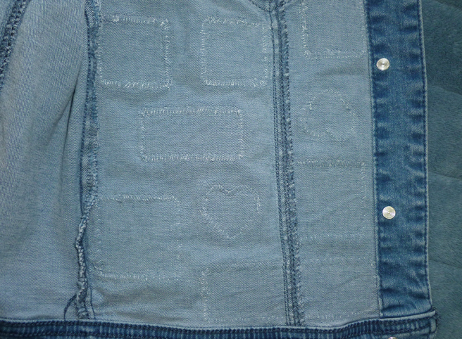 The inside of a light wash denim jacket. Rows of stitches in translucent nylon thread--like fine fishing line--show in the shape of the heart, square and rectangular patches attached to the other side, only just visible in the camera's flash.