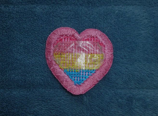 A pan pride - pink/yellow/blue - heart patch sitting on a blue micofibre blanket, reverse side facing upwards. A piece of double-sided tape has been placed on the back of the patch, the corners folded so the tape contours to the shape of the heart.