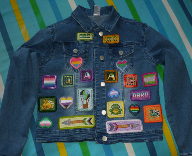 "A light wash, blue, cropped denim jacket sitting on a blue, white, yellow, green, navy and cyan striped quilt cover. The front of the jacket is covered in an assortment of handsewn cross stitch patches, including the letters ""A"" in pride flag stripes, two arrow designs, hearts in various flag stripes, a frog, two dragons, a hot air balloon, the word ""abro"" and the words ""aro"" in upper and lower case type."