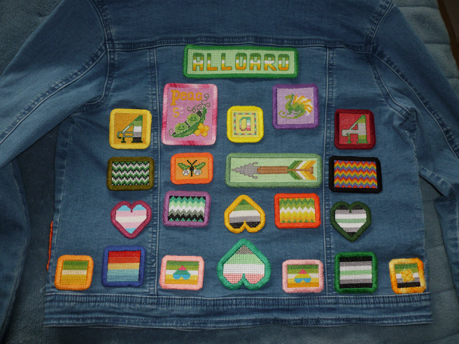 "The back of a light wash, blue, cropped denim jacket. The jacket back is covered in an assortment of handsewn cross stitch patches, including the letters ""A"" in pride flag stripes, an arrow design, hearts in various flag stripes, rectangle zigzag patches in various pride stripes, a dragon, square patches in various pride stripes, a patch with a cute pea design and a large text patch reading ""alloaro""."