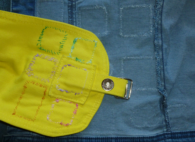 The inside of a light wash denim jacket. Rows of stitches in translucent nylon thread--like fine fishing line--show in the shape of the heart, square and rectangular patches attached to the other side, only just visible in the camera's flash. The inside of a yellow canvas packback sits partly atop the jacket, showing the same interior stitches--this time in pink, purple, green and gold embroidery floss. The floss stitches stand out very obviously against the yellow canvas.