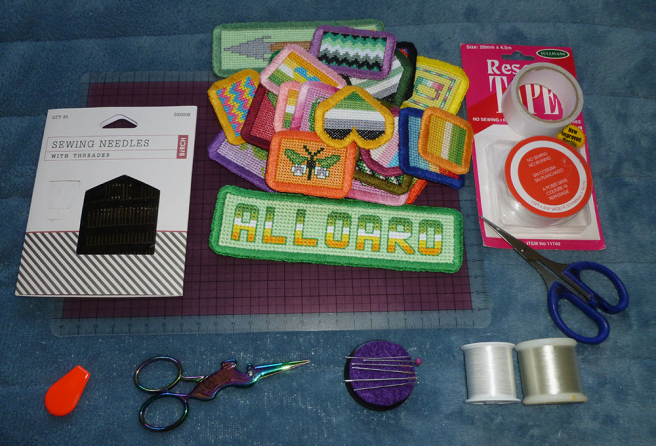 A variety of sewing tools sitting on a blue microfibre blanket. Tools include: a square plastic ruler, a pack of sewing needles, two spools of transparent nylon sewing thread, a needle threader, a unicorn-shaped pair of embroidery scissors, an assortment of needles on a purple felt needle keeper, a pair of plastic-handled household scissors, two spools of adhesive mending/rescue tape, and an assortment of cross-stitch patches.