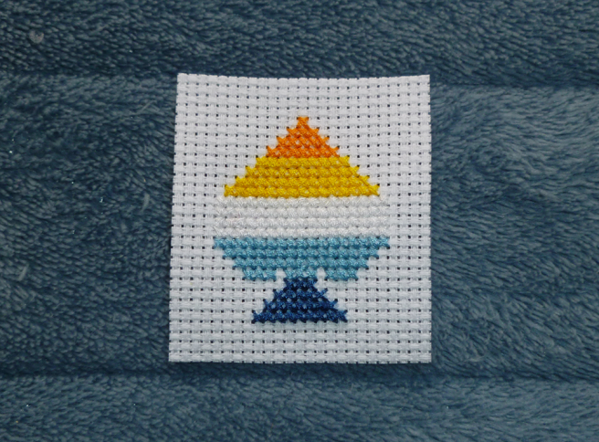 A white swatch of aida sitting on a blue microfibre blanket. Cross stitched onto the aida, in the shape of an ace of spades, is a five-striped aro-ace pride flag in orange, yellow, white, blue and navy.