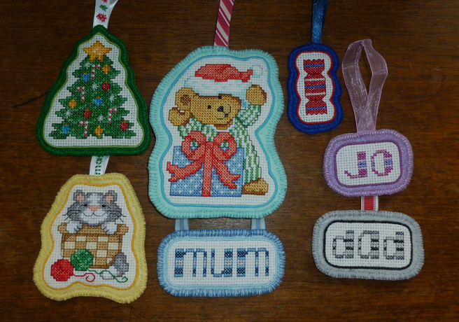 A collection of handsewn tree ornaments, with a cross stitch piece on aida sewn onto a matching felt background with a ribbon attached at the top for hanging. Several feature commercial kit patterns, including a Christmas tree, a kitten in a basket, a bear wearing a santa hat and a wrapped sweet. Three others feature the words mum, dad and jo sewn using the above letter patterns, in colourways of blue, purple/pink and black/grey.