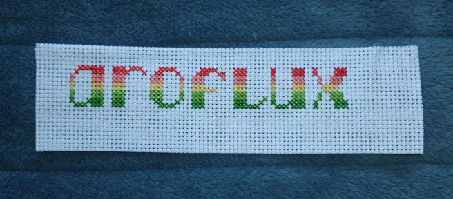 A white aida swatch, sitting on a blue microfibre blanket, with the text aroflux cross stitched in the colours of the pink/coral/lemon/light green/darker green aroflux pride flag.
