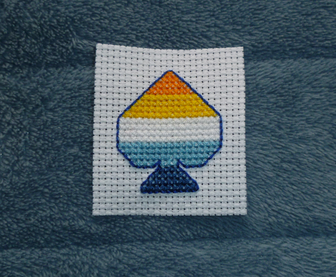 A white swatch of aida sitting on a blue microfibre blanket. Cross stitched onto the aida, in the shape of an ace of spades, is a five-striped aro-ace pride flag in orange, yellow, white, blue and navy. The spade is surrounnded by a backstitched outline in dark blue.