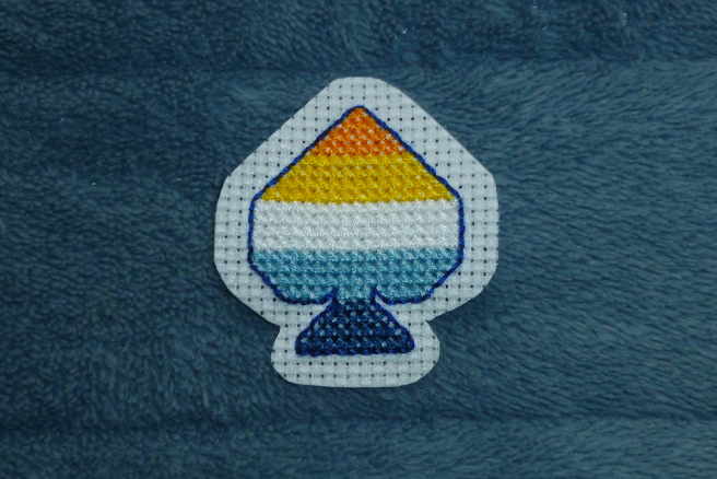 A cross stitch patch in progress sitting on a blue microfibre blanket. The patch, in the shape of an ace of spades, is a five-striped aro-ace pride flag in orange, yellow, white, blue and navy. The spade is surrounnded by a backstitched outline in dark blue, and the patch has been trimmed so a thin (somewhat uneven) border of white aida cloth extends around it.