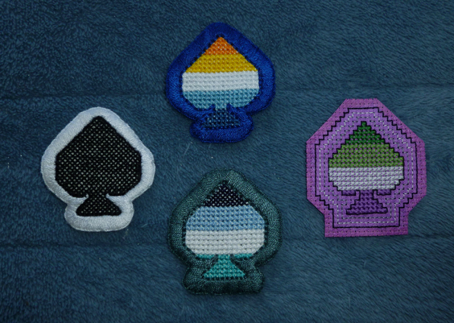 Four cross stitch patches, shaped like the ace of spades from a deck of cards, sitting on a blue microfibre blanket. Three of them have a thick buttonhole stitched edge, sewn on white aida; the fourth has a raw edge surrounded by decorative backstitching, sewn on purple aida. Flags featured: orange/yellow/white/blue/navy aro-ace flag (blue border), navy/blue/white/aqua oriented aro-ace flag (teal border), green/light green/white/purple (on purple aida). The last patch is a solid black with a white border.