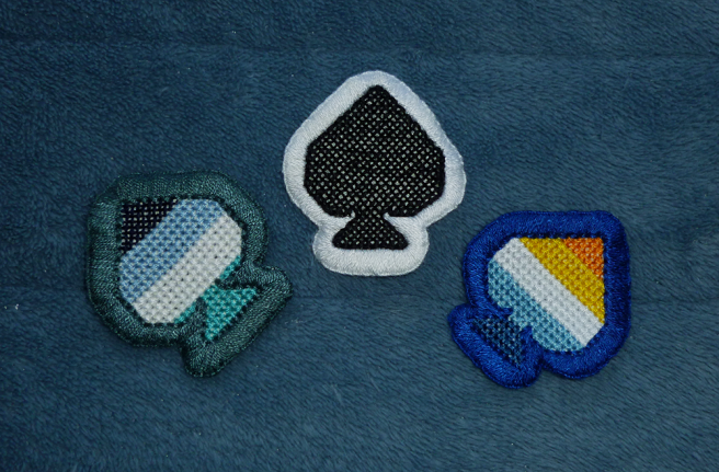 Three cross stitch patches, shaped like the ace of spades from a deck of cards, sitting on a blue microfibre blanket. All have a thick buttonhole stitched edge, sewn on white aida. Flags featured include the orange/yellow/white/blue/navy aro-ace flag (blue border) and the navy/blue/white/aqua oriented aro-ace flag (teal border). The last patch is a solid black with a white border.