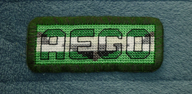 """A finished patch, sitting on a blue microfibre blanket, with the block letters """"aego"""" cross stitched in the colours of the black/grey/white/green (with triangle in reverse colours) aego flag and a matching background. The letters are outlined in a thick black floss, helping them stand out from the background. The patch is edged with a mottled green and black buttonhole stitch."""