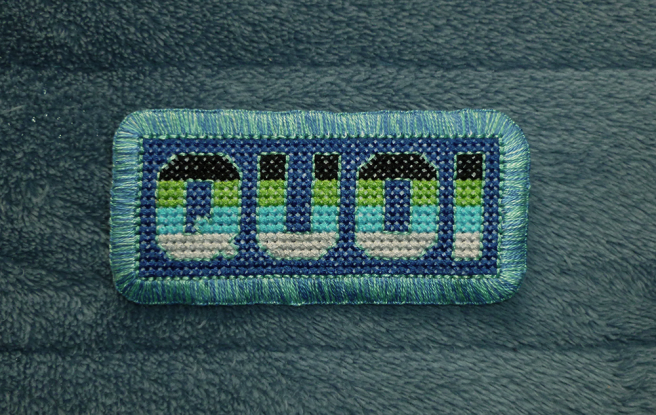 """A finished patch, sitting on a blue microfibre blanket, with the block letters """"quoi"""" cross stitched in the colours of the black/lime/cyan/grey quoiromantic pride flag on a blue background. The letters are outlined in light aqua floss. The patch is edged with a mottled blue and light aqua buttonhole stitch."""