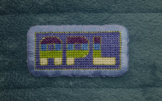 """A finished patch, sitting on a blue microfibre blanket, with the block letters """"apl"""" cross stitched in the colours of the purple/blue/lime/cream aplatonic pride flag on a lilac background. The letters are outlined in light lime floss. The patch is edged with a mottled sky blue and lilac buttonhole stitch."""