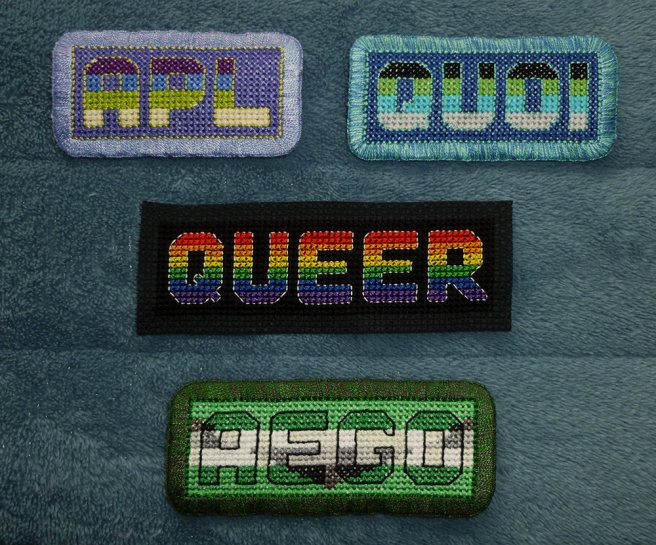 Four cross stitch patches, three finished and one unfinished, sitting on a blue microfibre blanket. All feature block capital letters sewn in their respective pride flags: apl (aplatonic), quoi (quoiromantic), aego (aegoromantic) and queer (rainbow/LGBTQIA+), with each letter outlined in backstitch. The apl, quoi and aego patches are finished with a buttonhole-stitch embroidered edging, while the queer patch is sewn on a piece of black, untrimmed aida cloth.