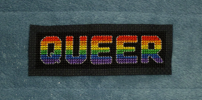 """An unfinished patch, sitting on a blue microfibre blanket, with the block letters """"queer"""" cross stitched in the colours of the red/orange/yellow/green/blue/purple rainbow/gay/LGBTQIA+ pride flag on a black background The letters are outlined in white floss. The raw black edges of the aida have not yet been trimmed or embroidered."""