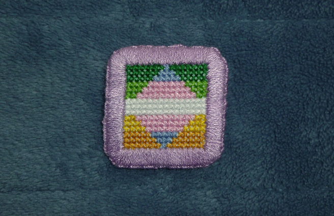 A square cross stitch patch sitting on a blue microfibre blanket. The patch depicts the allo-aro pride flag (green/light green/white/yellow/gold horizontal stripes) with a centre rhombus depicting the trans pride flag (blue/pink/white/pink/blue horizontal stripes) set so that both flags share the middle white stripe. The patch is edged with a thick buttonhole stitch in lilac.