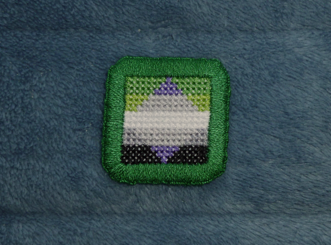 A square cross stich patch sitting on a blue microfibre blanket. The patch depicts the aro pride flag (green/light green/white/grey/black horizontal stripes) with a centre rhombus depicting the greysexual pride flag (purple/grey/white/grey/purple horizontal stripes) set so that both flags share the middle white stripe. The patch is edged with a thick buttonhole stitch in dark green.