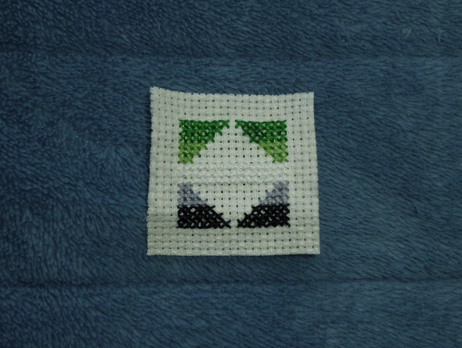 A square scrap of off-white aida, forming a patch in progress, sitting on a blue microfibre blanket. The aro pride flag (green/light green/white/grey/black horizontal stripes) has been sewn onto the fabric in triangular sections, leaving a centre rhombus bare save for a centre white stripe. The image looks like two blank triangles, divided by a strip of white, against a background of green/light green on top and grey/black on the bottom.