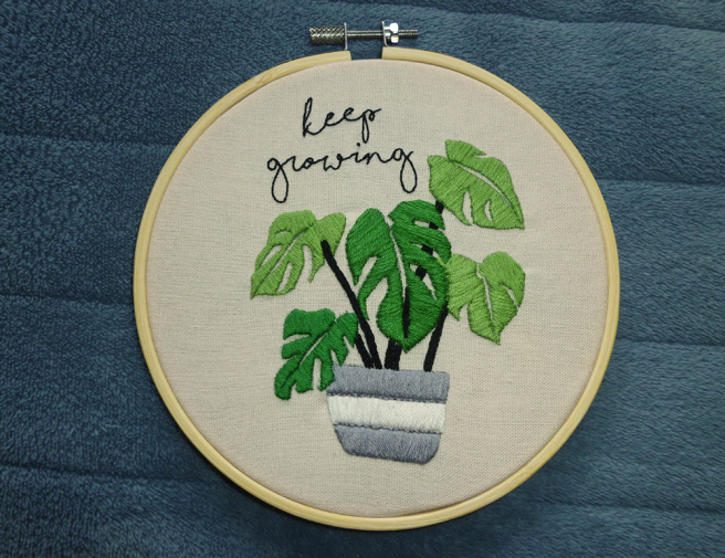 "A bamboo embroidery hoop sitting on a blue microfibre blanket. The hoop is filled with cream cloth featuring an embroidered monstera plant growing in a grey and white striped pot, with script text reading ""keep growing"" in black backstitch. The pot and the leaves of the monstera plant--sewn in light and medium green-are filled with satin stitch, while the black stems are sewn in repeated chains of very fine split stitch. All colours used in the piece are from the aromantic flag."