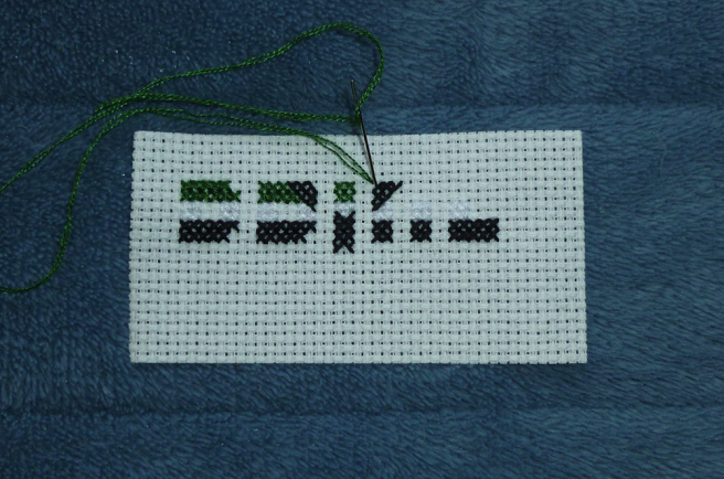 """A white aida swatch, sitting on a blue microfibre blanket, with parts of the letters """"p"""", """"r"""", """"i"""" and """"d"""" sewn in the first three stripes of the cross apothiromantic flag (dark green, white and black). Parts of an upward-reaching cross extend out from the """"i"""" (the center of the to-be-sewn word """"pride""""). The photo shows a needle, threaded with green, coming up from a left-hand square in the aida and descending into the middle of a half stitch in black."""