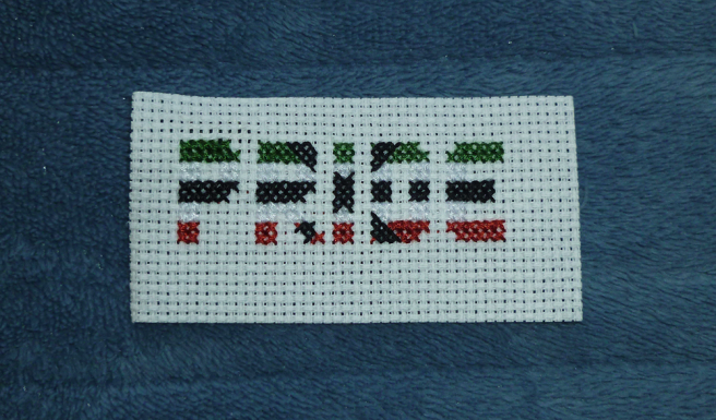 """A white aida swatch, sitting on a blue microfibre blanket, with the rough shapes of the letters forming the word """"pride"""" in the colours of the cross apothiromantic flag (dark green, white, black, white, red). An angled cross sewn in black extends out from the centre """"i"""", its diagonal edges sewn with black three-quarter stitches meeting green, red and white quarter stitches."""