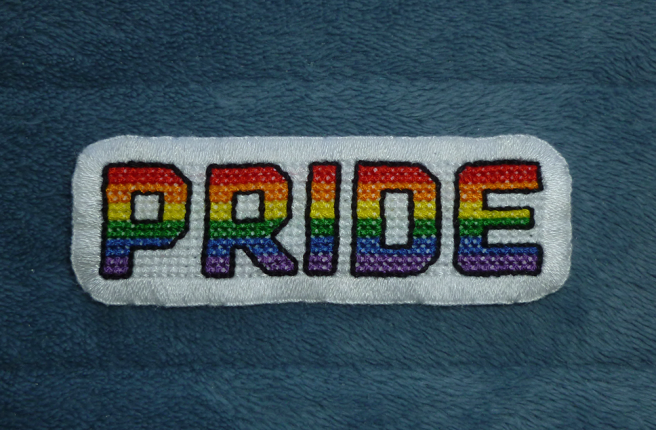 """A finished patch, sitting on a blue microfibre blanket, with the block upper-case letters """"pride"""" cross stitched in the colours of the red/orange/yellow/green/blue/purple LGBTQIA+/queer/rainbow pride flag on a white background. The letters are outlined in thick black floss. The patch is edged with white buttonhole stitch."""