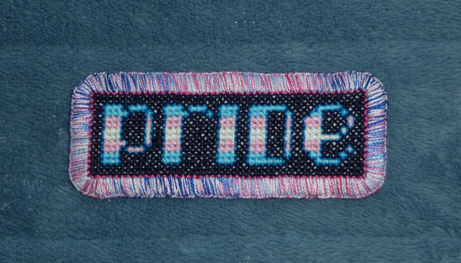"""A finished patch, sitting on a blue microfibre blanket, with the pixel-art-style lower-case letters """"pride"""" cross stitched in the colours of the blue/pink/white/pink/blue transgender pride flag on a navy background. The letters are outlined in bright blue floss. The patch is edged with a mottled blue, white and pink aqua buttonhole stitch."""