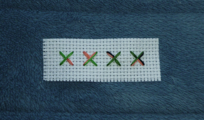 A narrow white aida swatch, sitting on a blue microfibre blanket, showing four examples of fractional cross stitches. Example one: a modified three-quarter stitch with a quarter and half stitch sewn in green and a quarter stitch sewn in peach. Example two: a traditional three-quarter stitch with a half stitch and a quarter stitch sewn in both green and peach. Example three: a three quarter stitch with a half and quarter stitch sewn in green and a quarter stitch sewn in black and peach. Example four: a three quarter stitch sewn in green and a three quarter stitch split in half with one side sewn in peach and the other black.