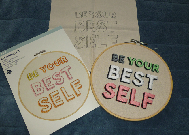 """A bamboo embroidery hoop sitting on a blue microfibre blanket. The hoop is filled with cream cloth featuring the text """"be your best self"""" with each word satin stitched in grey, mint, white and pink taken from the idemromantic pride flag. Each word is outlined by back stitch in a slightly darker or lighter shade of grey, mint, white and pink, and given a three-dimensional/shadow effect via more black satin stitch. Beside the hoop sits another piece of cream cloth, with the same text printed in black ink and waiting to be sewn. The cardboard front of the kit packaging is also visible, showing the text sewn in yellow, pink and orange--this time with the letters outlined in back stitch and the shadow filled in with satin stitch."""