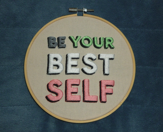 """A bamboo embroidery hoop sitting on a blue microfibre blanket. The hoop is filled with cream cloth featuring the text """"be your best self"""" with each word satin stitched in grey, mint, white and pink taken from the idemromantic pride flag. Each word is outlined by back stitch in a slightly darker or lighter shade of grey, mint, white and pink, and given a three-dimensional/shadow effect via more black satin stitch."""