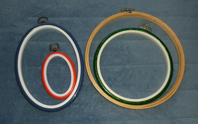 Four embroidery hoops/frames sitting on a blue microfibre blanket. Left: two plastic oval-shaped frames with white plastic inner rings and brass D-shaped hooks. The larger frame has a blue outer ring, the smaller red. Right: a wooden 20 cm hoop with a brass screw and a green-embedded-with-gold glitter plastic 15 cm frame. The plastic frame has a white inner ring and a gold D-shaped hook. The smaller hoops/frames sit inside the larger.