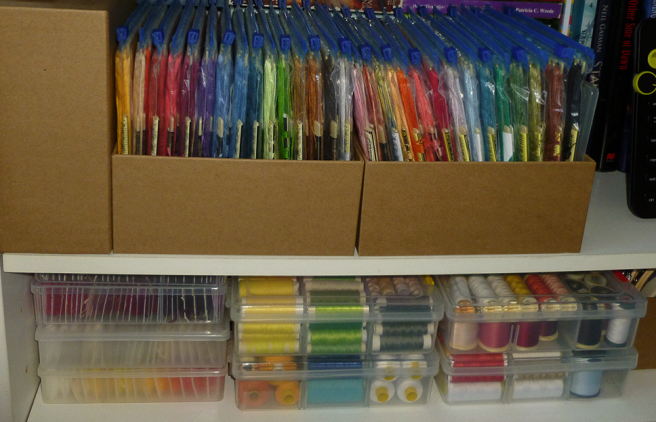 A white laminate bookcase with two shelves showing. Bottom shelf: clear divider/compartment boxes of several sizes containing floss wound onto bobbin cards and spools of thread ranging from Gutermann and DMC machine embroidery thread to cheap polyester. Top shelf: embroidery floss housed on ecru plastic stitchbows by DMC, the stitchbows arranged inside clear ziplock bags. The bags sit in rows inside plain square cardboard boxes.