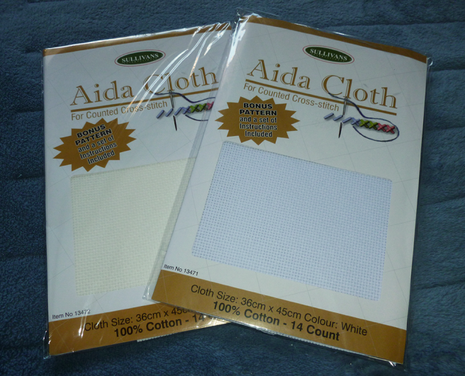 """Two new packages of Sullivans brand aida sitting on a blue microfibre blanket. The label reads """"Aida Cloth For Counted Cross Stitch"""" and lists the dimensions as """"36cm x 45cm"""", the size as """"14 count"""" and the material as """"100% cotton"""". One is a white with a slight grey undertone, while the other is """"natural"""", a cream with a slight yellow undertone. Both pieces of aida are housed inside clear plastic bags."""