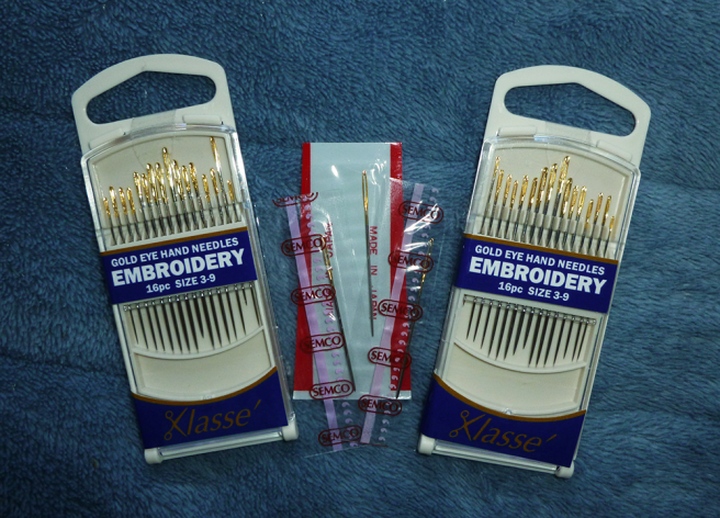 """Various new-in-package needles sitting on a blue microfibre blanket. Left and right: two cream plastic cassettes holding Klasse brand """"gold eye hand needles"""" for """"embroidery"""", size 3-6. Each cassette holds sixteen sharp needles with bright golden eyes. Centre: three size 24 tapestry needles with blunt ends. Two are inside clear plastic packets with """"semco"""" printed in brown; one is housed inside a packet with a white and red striped background. All three have golden eyes."""