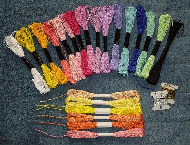 Several skeins of floss, arranged on a blue microfibre blanket. Top row: white, yellow, gold, coral, light pink, pink, magenta, purple-pink, lilac, lighter lilac, lavender, cyan, dark blue, mint, lime, black. All these have black paper bands. Bottom row: ecru, lemon, yellow, peach-orange, burnt orange, light pink. All these have white paper bands.