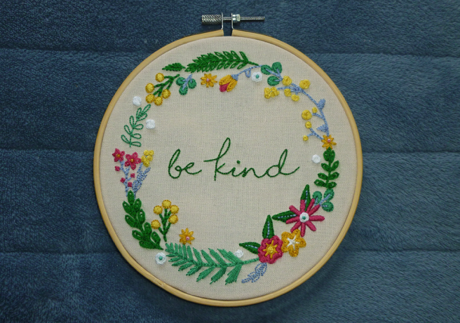 """A bamboo embroidery hoop sitting on a blue microfibre blanket. The hoop is filled with cream cloth featuring a garland of assorted flowers and leaves around the centre-positioned text """"be kind"""". The text is written in a loose, handdrawn type and backstitched in green. The leaves and stems are stitched in green, aqua or light blue, and feature a variety of black, chain, split, straight and satin stitches. The flowers are stitched in white, gold, yellow and dark pink, and feature a variety of chain, satin, straight, woven wheel and god's eye stitches. Small seed beads in pink, gold and aqua fill the centres of some flowers. All colours used in the piece are taken from @neopronouns's allosexual aromantic-spectrum flag."""